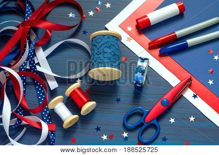 Set of materials for making handmade souvenirs and gifts by July 4 celebration of Independence Day. Paper ribbons and confetti are blue white and red. Glue markers scissors on blue background