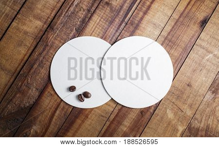 Two blank white beer coasters and coffee beans on wood table background. Responsive design mockup. Top view.