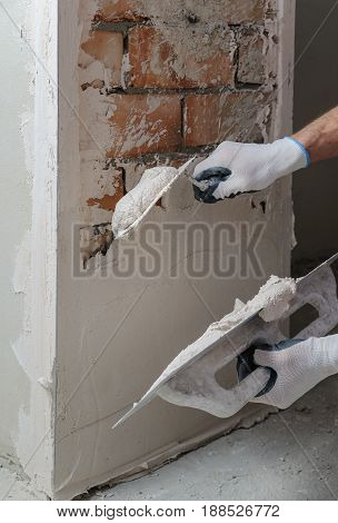 Worker's hands are using trowels for gypsum plaster.