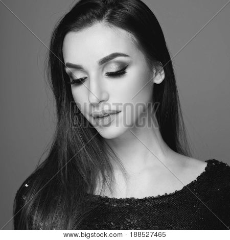 Closeup beauty studio fashion portrait of young beautiful girl with long brunette dark hair and nakeup posing in shiny green dress with sequins posing with closed eyes against purple background.