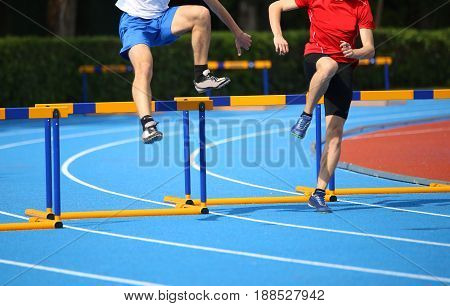 Two Boys Jumping Over Hurdles