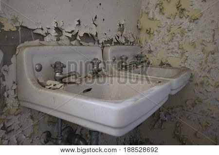 Peeling paint and two old sinks in an old asylum