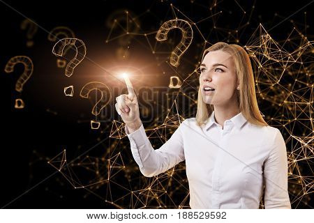 Portrait of a blonde businesswoman standing against an orange virtual reality background with a glowing index finger. Question marks and abstract lines