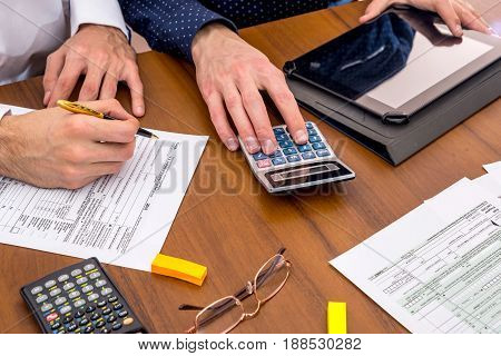 Two Mens Filling Usa Tax 1040 Form With Calculator, Tablet.