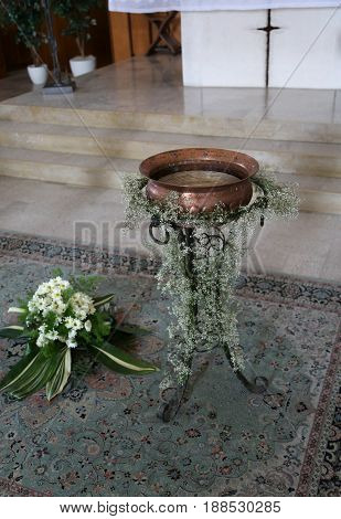 Small Baptismal Font In Copper Decorated With Flowers During The