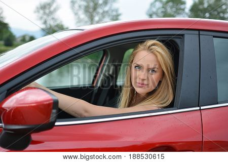Beautiful young blonde girl driving slowly and carefully brand new red car and looking through open window