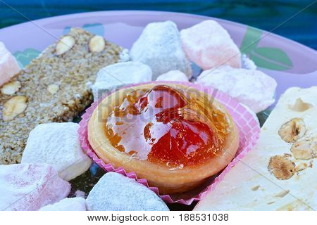 Candied cherries in punnet of dough served with Turkish delight and and halva close up view