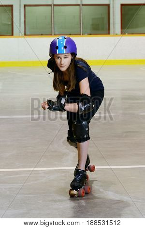 teen girl playing roller derby in a roller rink