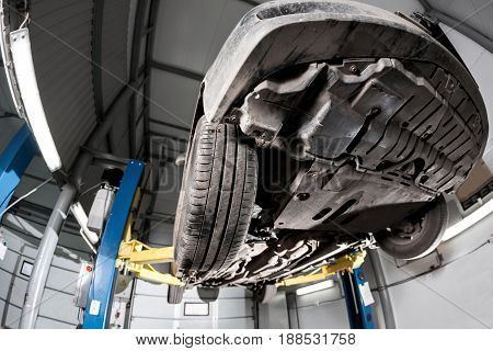 Auto view from the bottom. front car suspension. the garage mechanic raised the car on the lift.