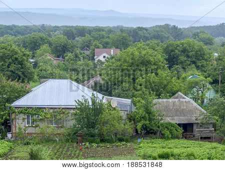The cottage top view with a kitchen garden and trees around. Further among trees also other houses are visible. Spring. Russia.