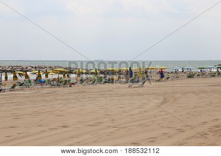 Umbrellas And Sunbeds By The Beach In Summer Resort For Holidaymakers