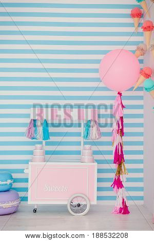 Children's zone with sweets: lollipops, ice cream, macarons, balloon and candy bar. Children room with blue stripe background.