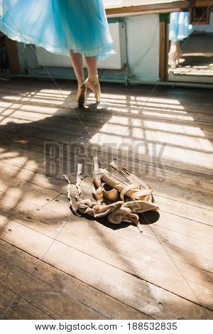 Young ballerina or dancer girl putting on her ballet shoes. Girl in a turquoise ballet skirt. Old ballet shoes on old wooden floor. Pink ballet pointe. Shadow from window on a wooden background.