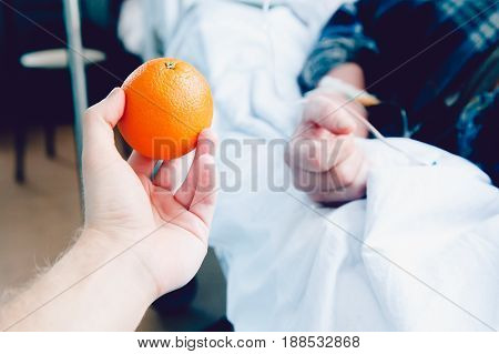 doctor's hand holds an orange against the patient's background. Concept treatment of oranges with vitamin C - useful fruit for health.