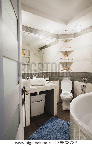 Interior design of a luxury bathroom, washroom with washbasin, huge mirror and seashells on the counter.
