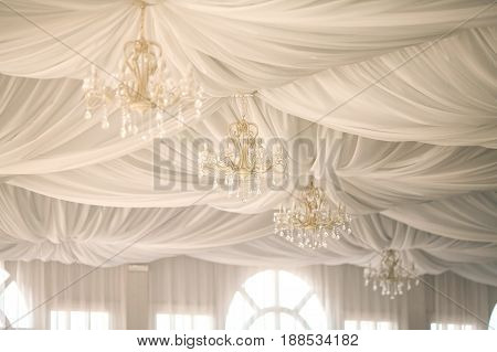 gold chandeliers on an tent's ceiling in a wedding party. wedding decor in a white tent.