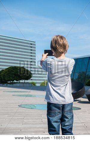 Child taking photo with his smartphone in the city. Back view.