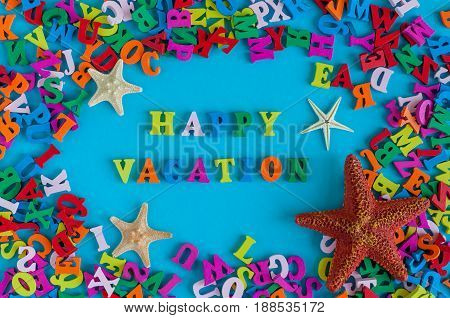 HAPPY VACATION - word composed of small colored letters. Summer vacation souvenir - starfish from tropical sandy ocean beach, holidays abroad - summertime top view concept.