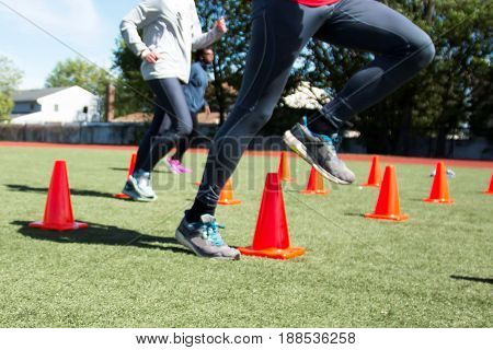 High school track and field athletes run over orange cones on a green turf field during practice