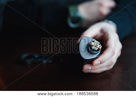 male master installs a coil. Spiral for electronic evaporator and cigarette. Vape, vaping. Firing a coil. Burns, styling