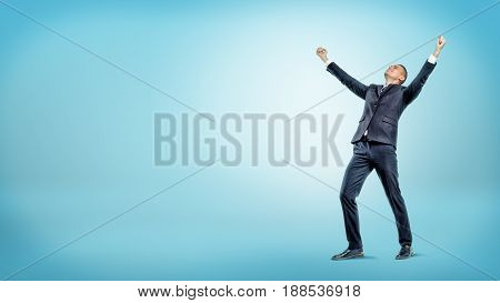 A joyful businessman standing with hands raised in victory and looking up on blue background. Happiness and joy. Successful meeting. Contract signing.