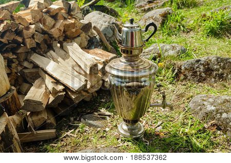 A silver samovar stands on the grass next to a pile of firewood. The samovar is equipped with a teapot.