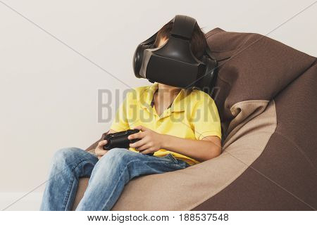 Boy Plays Game With Virtual Reality Glasses Indoors