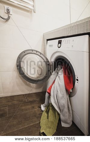 Washing machine with multicolored dirty towels inside. Side view. Vertical