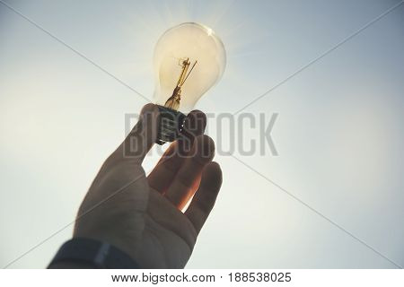 Menhand in light bulb the background of nature