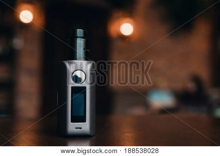 Close-up of electronic cigarette. vaping device. steam generator. high contrast and monochrome color tone.Vaping set on wooden table