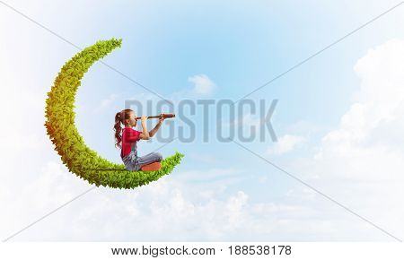 Cute kid girl on green moon in day sky looking in spyglass