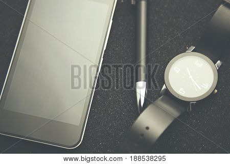 phone watch and pen on black table