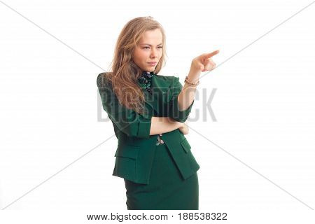 Beautiful blonde business lady in green uniform pointing aside isolated on white background