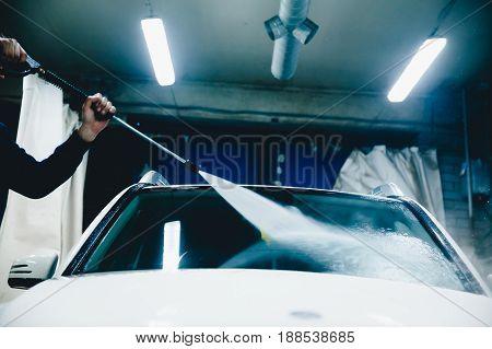 Closeup man wash car. Washing white car by high pressure water. Concept car cleaning.