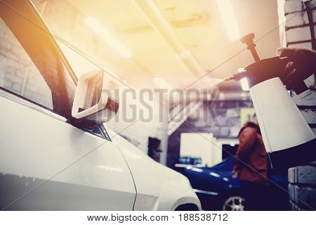 man working a car wash close up car cleans. Concept of washing a modern car with high-pressure water.