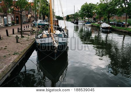 Monnickendam Netherlands - August 08 2016. Street view with old traditional houses and canal with ships moored in the dutch village of Monnickendam. The town was founded by monks and it is a small fishing village today