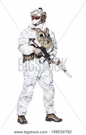Special forces operator of Navy Seals armed with assault rifle with closed face in polarized sunglasses and military winter camo clothes turning back. Studio shot