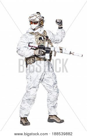 Special forces operator of Navy Seals armed with assault rifle with closed face in winter camo clothes using visual hand and arm signal to control the movement of his team. Studio shot