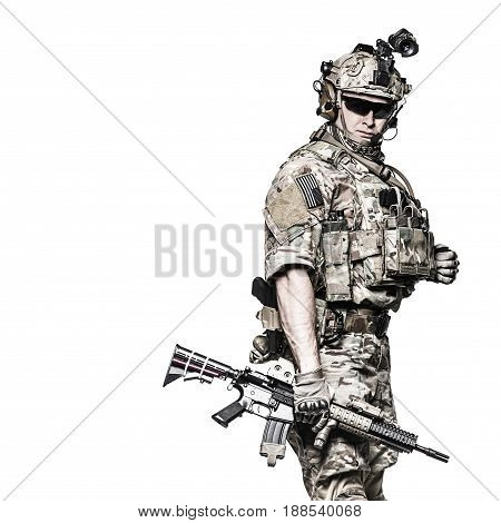 Elite member of US Army rangers in combat uniforms with his shirt sleeves rolled up, in helmet, eyewear and night vision goggles. Studio shot, white background, looking at camera, dark contrast