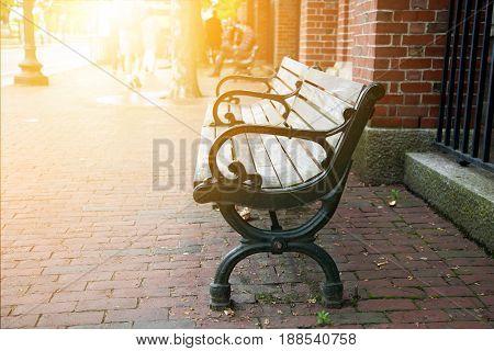 Black park bench with sunlight at sidewalk in boston.