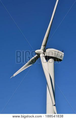 Wind turbine closeup on the blue sky background