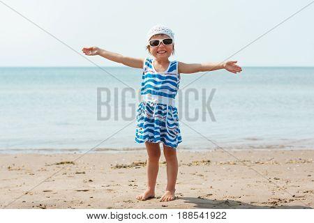 Happy cute little girl on the seashore