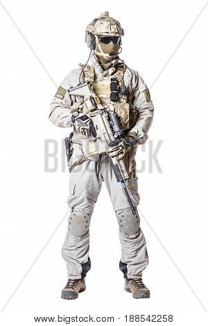 Army soldier in Protective Combat Uniform holding Special Operations Forces Combat Assault Rifle. Knee pads, mag recovery pouch, chest rig, military boots. Studio shot, isolated on white