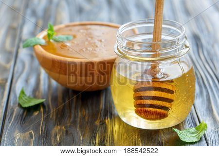 Glass Jar And A Wooden Bowl With Natural Honey.
