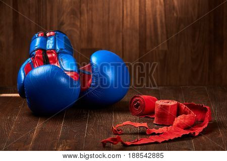 Blue and red boxing gloves with two rolls of hand bandage on wooden background. Bright sportwear against brown wooden background. Horizontal photo and close-up. Sportive training and exercise. Concept of the sportive healthy lifestyle.