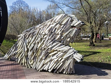 MOSCOW RUSSIA APRIL 29 2017: A funny sculpture of a large white furry dog. The entrance to Pushkin's pedestrian bridge. Moscow Russia. Sunny day in April.
