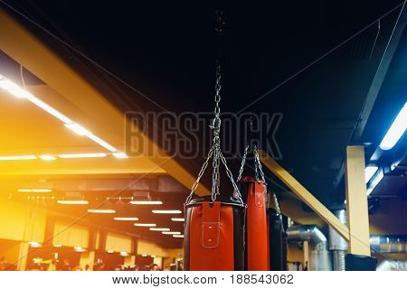 Punching bag in the gym. Against the backdrop of athletes. Gym is a cellar. high contrast and monochrome color tone.