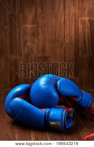 Boxing background with blue gloves and red bandage on wooden background. Pair of the boxing gloves. Colorful sportwear and accessories. Vertical photo. Energy, power and victory. Concept of the healthy lifestyle.