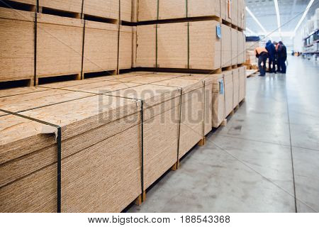 Sawn timber. Drywall, dvp, chipboard, Shelf with structural materials on the shelves in the construction warehouse.