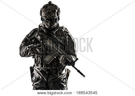 Army soldier in Protective Combat Uniform holding Special Operations Forces Combat Assault Rifle. Studio shot, dark contrast, cropped, desaturated, isolated on white background